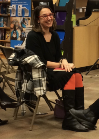 Sonya sitting in a chair grinning wearing orange tights and black boots