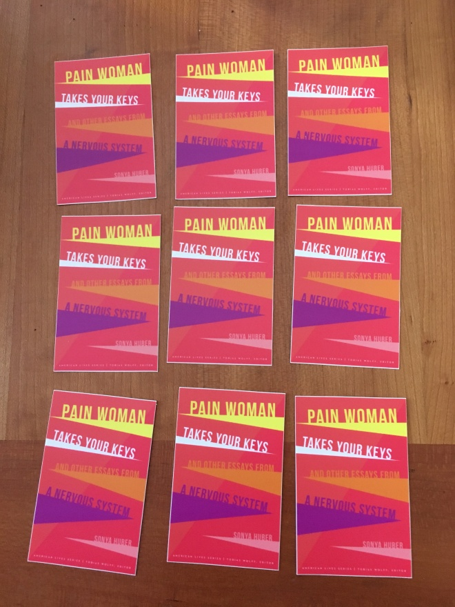 A collection of nine stickers of the cover of Pain Woman in three rows of three on a table. The cover itself is a series of colorful triangles reaching toward the center on a red background.