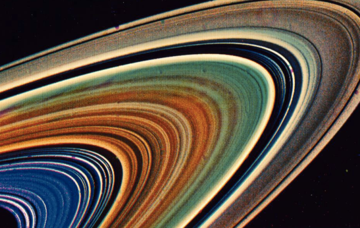 Rings of Saturn with colors enhanced to show their differences; bands of blue, then red, then greenish, then tan. Thank you, NASA.