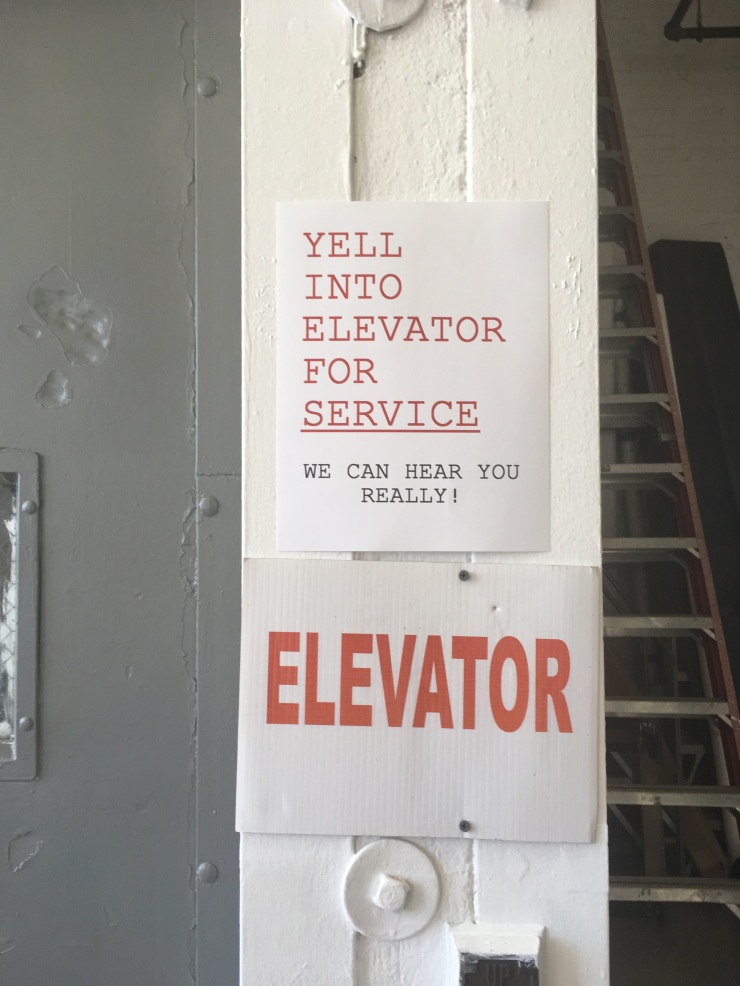 "Image of two signs on a white wall. One says ""Elevator"" and the other says ""Yell into elevator for service. We can hear you really!"""