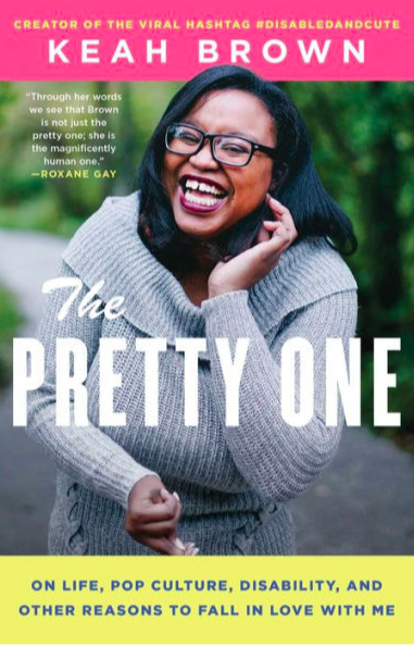 Cover of Keah Brown's The Pretty One, with author name in white on a pink field at the top, above a picture of Keah, wearing glasses and laughing as she curls some hair behind her ear. She is wearing a gray cowl-necked sweater, and her other hand is curled in front of her stomach. The background is a blurred forest scene beside a roadway.
